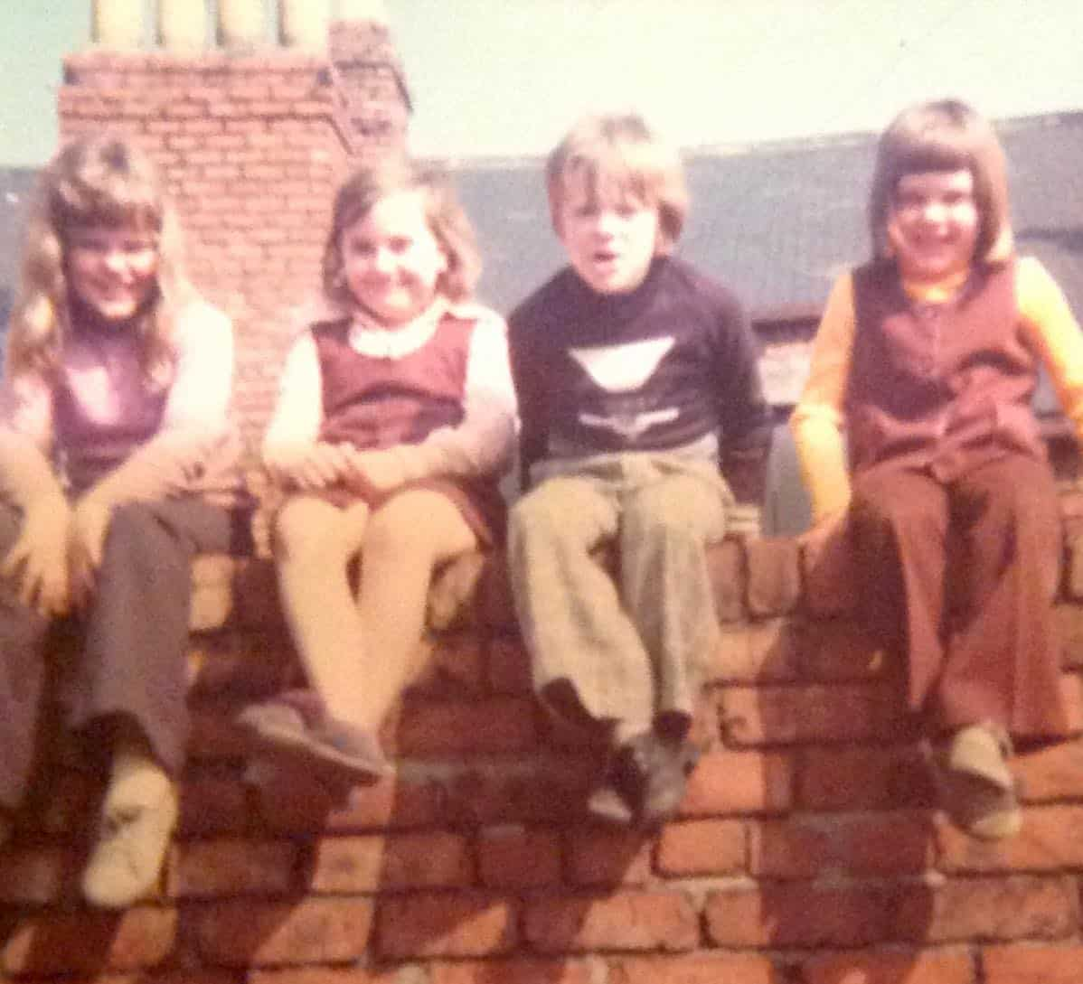 children sitting on a back wall in the 1970s